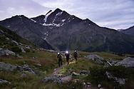 """Il gruppo """"Sulle tracce dei ghiacciai"""" guidato da Fabiano Ventura durante un ascesa all'alba. Il gruppo si è messo in cammino prima del sorgere del sole in modo da poter raggiungere in tempo la cima del monte Confinale dove riprodurranno, fotograficamente, le foto di fine '800 dei ghiacciaio del Forni e del gran Zebru. Lombardia, Agosto 2020"""