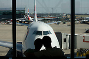 "Honeymooners cuddle in front of their Boeing 747-400 that will soon take them on a round-the-world adventure, leaving from Heathrow Airport's Terminal 5B. The couple are seen as silhouettes against the natural light of the large plate glass windows. As the aircraft is readied and before the flight's air travellers are called to the departure gate, the young man and woman put their heads imagining what new things they will see as their airliner is about to transport them to experience new cultures and possibly a new life. In the background, we see other jets that are parked in their respective jetties across the main movement area, the apron. From writer Alain de Botton's book project ""A Week at the Airport: A Heathrow Diary"" (2009)."