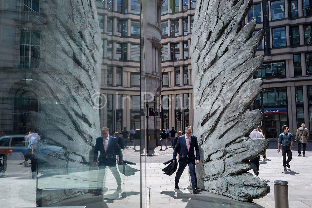 A financial industry businessman  walks past the sculpture entitled City Wing on Threadneedle Street in the City of London, the capitals financial district aka the Square Mile, on 11th July 2019, in London, England. City Wing is by the artist Christopher Le Brun. The ten-metre-tall bronze sculpture is by President of the Royal Academy of Arts, Christopher Le Brun, commissioned by Hammerson in 2009. It is called 'The City Wing' and has been cast by Morris Singer Art Founders, reputedly the oldest fine art foundry in the world.