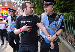 """© Licensed to London News Pictures . 28/08/2021. Manchester, UK. Police remove a man wearing an anti-trans LGB Alliance t-shirt as he stood amongst demonstrators at the pro-trans-rights demo. People take part in a Reclaim Pride march through Manchester City Centre , in opposition to the management of the city's """"official"""" Manchester Pride charity festival . The Manchester Pride charity parade was cancelled in 2020 due to Coronavirus . An """"equality march"""" organised by Manchester Pride charity was due to take place on Deansgate as the protest passed through the Gay Village . Protesters object to Manchester Pride charity's withdrawal of funding for the LGBT Foundation's condom distribution scheme and HIV charity George House Trust as well as increasing commercialisation of the annual event . Photo credit: Joel Goodman/LNP"""