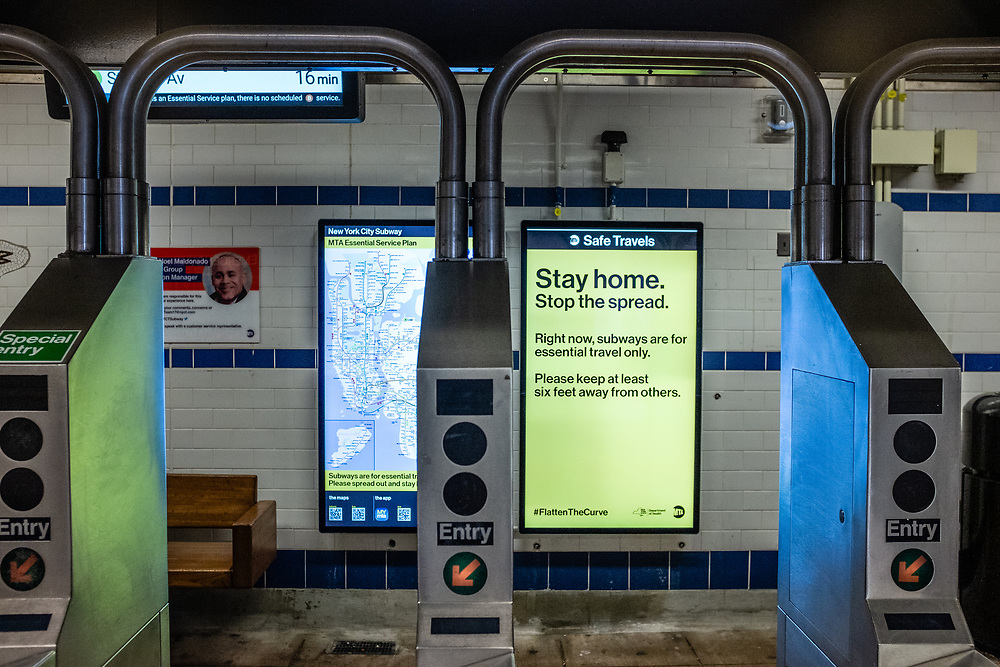 Brooklyn, NY. 5 April 2020. Signs in the entrance to the Avenue J station on the subway's Q line announce service restrictions, and ask that all non-essential riders stay home. This sign asks people to stay home, and maintain a social distance of at least 6 feet (2 meters).