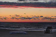 Gull flies overhead while lifeguard chair and lifeboat lie on the beach at daybreak.