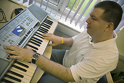 Day service user with learning disability playing a electric organ,