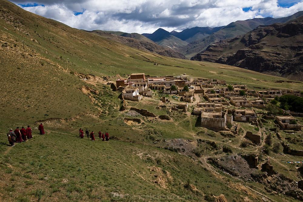 Monks walk towards a partially rebuilt monastery in the Tibetan Plateau.