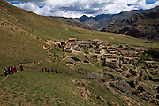 Monks walk towards a partially rebuilt monastery in the Tibetan Plateau.