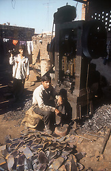 Metal work shop in the Punjab; India; with worker using press,