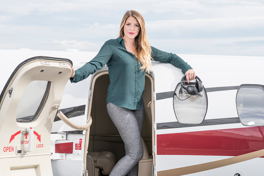 Woman posing while exiting a jet holding the Bose QC35 with Nflightmic attached. Nflightmic lifestyle photo shoot created by Arkansas based commercial photographer, Alex Kent