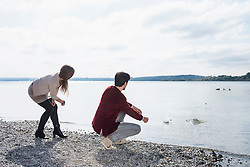 Young couple lake skimming stones