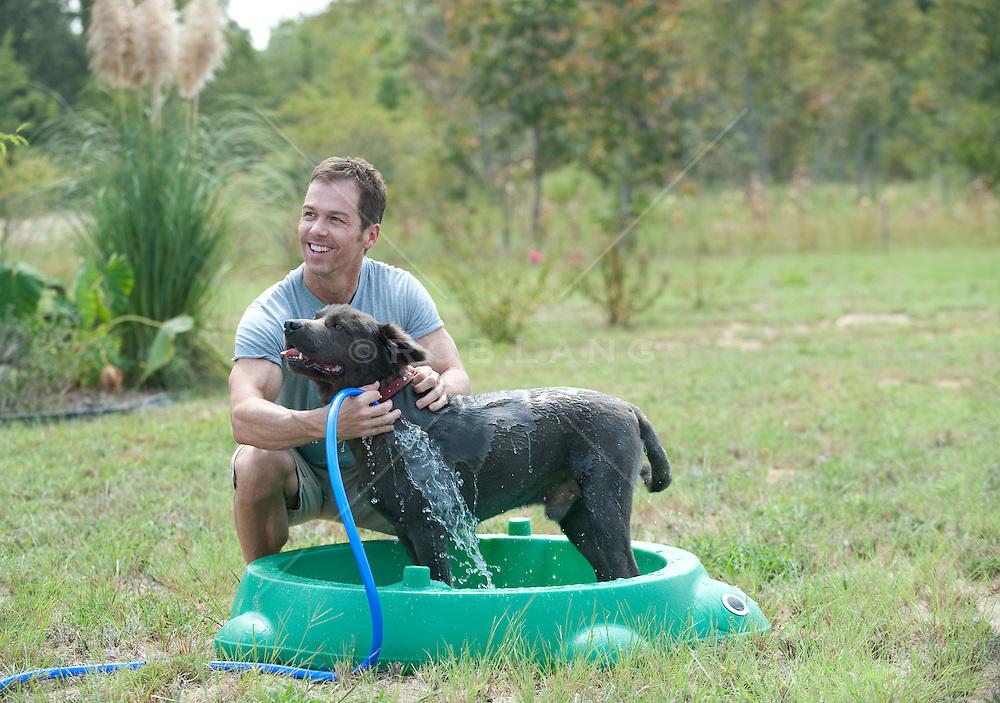 man outdoors giving a dog a bath