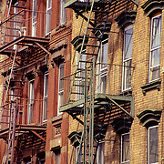 Modernized tenement buildings with distinctive fire escapes, housed large numbers of immigrants in the last 19th and early 20th centuries, typical of Manhattan and Brooklyn.