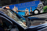 A taxi cab and a parked tour coach for Platinum Holidays features famous London landmarks, both awaiting passengers outside a London theatre.
