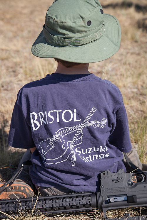 """A boy sits with his weapon as several hundred gun-rights supporters gather in a parking lot before marching with their weapons down Main Street in Westcliffe, Colo., as part of an Independence Day Parade. Many brought their children. A few brought animals. A flyer promoting the armed march was circulated throughout southern Colorado, calling on """"patriots"""" to bring their guns - especially the """"evil black ones"""" - and display them in the annual parade."""