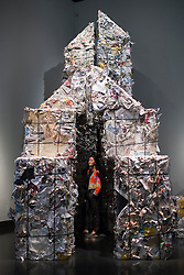 © licensed to London News Pictures. London, UK 17/06/2013. A spectator looking at Erik Kessels' small house made of recycled paper at the V&A's Sky Arts Ignition: Memory Palace exhibition on Monday, 17 June 2013. The V&A commissioned the author Hari Kunzru to write an original short story which has been transformed into a 'walk-in book' by 20 graphic designers, comic book artists, illustrators and typographers. Photo credit: Tolga Akmen/LNP