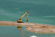 The evaporation pools at the Dead Sea Works (DSW), Dead Sea, Israel with a yellow hydraulic Excavator
