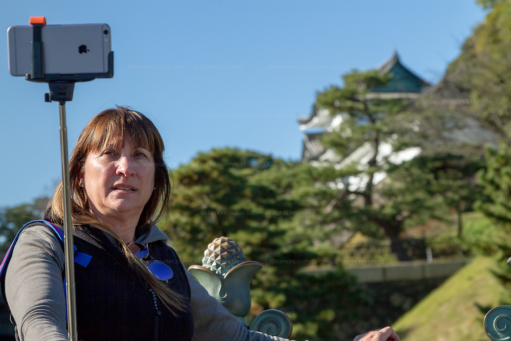 A western tourist with a selfie stick and an iPhone takes a selfie at the Imperial Palace in Tokyo, Japan. Friday December 18th 2015