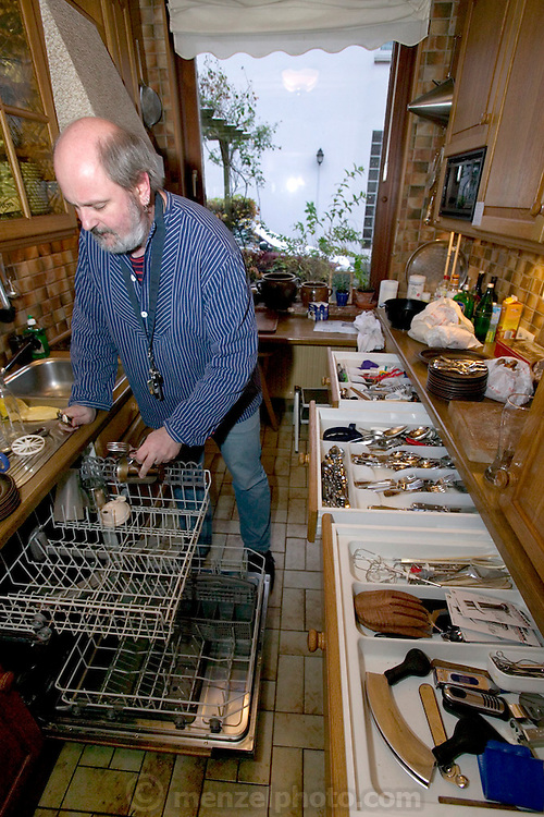 (MODEL RELEASED IMAGE) Jörg Melander empties the dishwasher in his home kitchen in Bargteheide, Germany. (Supporting image from the project Hungry Planet: What the World Eats.)