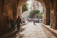 Pedestrians and a motorcyclist pass under an arched corridor on a street in Islamic Cairo, the architectural heart of medieval Cairo, Egypt.