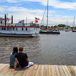 Annapolis, MD, USA - May 20, 2012: Couple Sitting on the dock at the Annapolis Harbor
