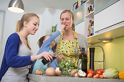 Mother and daughter flavor salad while son feeding mother