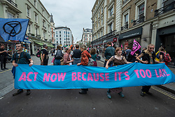 © Licensed to London News Pictures. 23/08/2021. LONDON, UK.  Protesters hold up a banner on Cranbourn Street as climate activists from Extinction Rebellion stage protest in Covent Garden.  The group has announced that it will stage protests in the capital for the next two weeks as they try to raise awareness of the effects of big business on climate change.  Photo credit: Stephen Chung/LNP