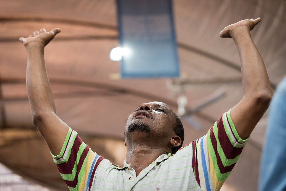 27 October 2019, Addis Ababa, Ethiopia: A man raises his arms in prayer during Sunday service at the Finfinne Oromo Mekane Yesus Congregation of the Ethiopian Evangelical Church Mekane Yesus. In a context where congregations did not use to be allowed to hold their services in any language but Amharic, the congregation today is one of some 60 Oromo speaking Mekane Yesus congregations in Addis Ababa. The service takes place on the first Sunday following political turmoil in the country, claiming dozens of lives.