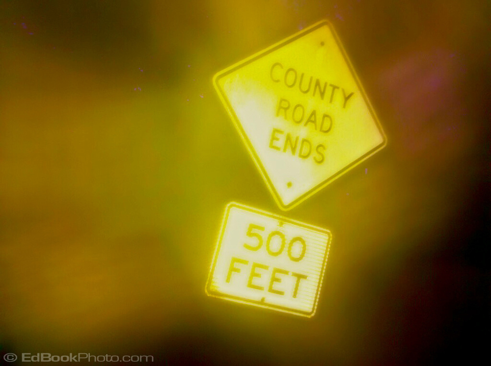 a county road ends sign glows in fog