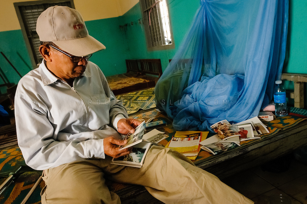 Land mine survivor, arranging photos of family and friends, Siem Reap, Cambodia