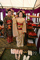 Geishas (maiko) prepare for a performance at the  Kitano-Tenmangu Shrine, Kyoto, Japan