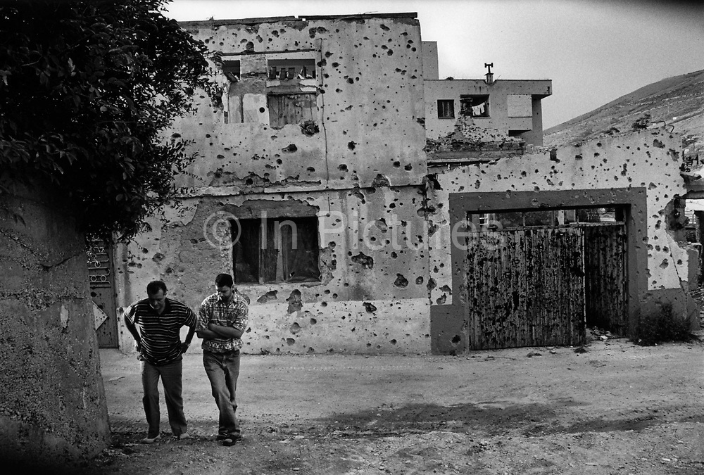 """People returning to some sense of normality amidst the ruins after the Dayton Peace Accords. It was destroyed by systemic bombardment from Croat guns during the Croat Muslim War, when the Croats endeavored to """" cleanse"""" the town of non Croats. Mostar, Bosnia and Herzegovina."""