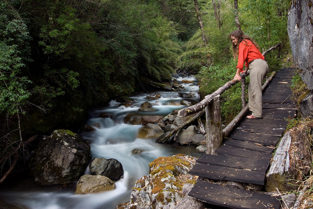 Woman gazing at a mountain stream from a boardwald on a trail in Patagonia, Chile.