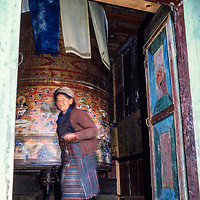 A Sherpa woman turns a big prayer wheel at the gompa (temple)at Namche Bazar  in the Khumbu region of Nepal 1986.