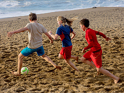 Girl and boys playing soccer on shore at the beach
