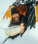 Mark Gabites, passes dinner between two tents during storm, skiing to K2, Baltoro glacier, winter, Karakoram, Pakistan