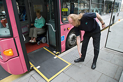 Bus driver putting out ramp for wheelchair user,