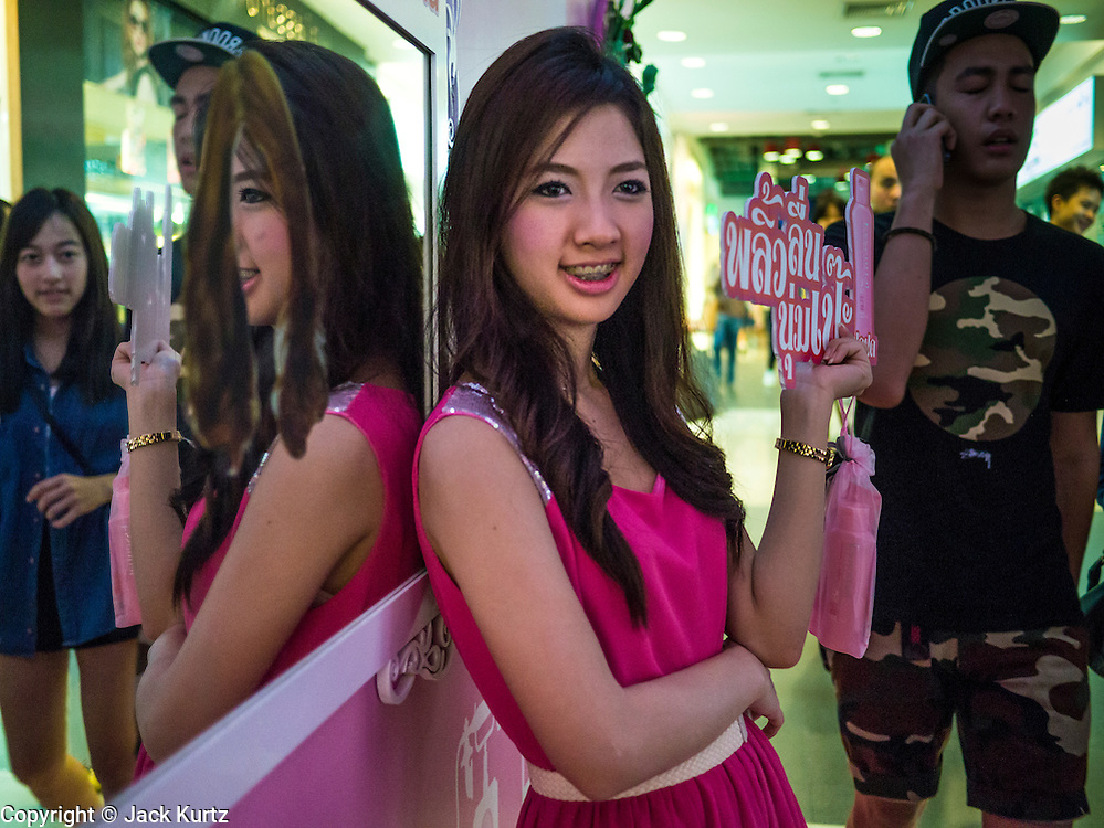 06 JULY 2013 - BANGKOK, THAILAND:  A Thai woman hands out promotional literature for a cosmetics company in Siam Square, a shopping center in Bangkok.      PHOTO BY JACK KURTZ