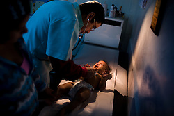 Dr. Carlos Serrano checks Lizmari Ahumada, 8 months, at his clinic  in Petare, one of the largest and most dangerous slums of Caracas.  Pfizer is trying to increase their market share in the slums and are targeting clinics, hospitals and pharmacies, sending sales representatives to the far reaches of the slum. Dr. Serrano receives regular sales calls from Pfizer representatives.