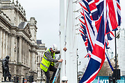 """January 30, 2020, London, England, United Kingdom: A man is mounting British Union flags outside Parliament near the statue of Winston Churchill in London, Thursday, Jan. 30, 2020. Although Britain formally leaves the European Union on Jan. 31, little will change until the end of the year. Britain will still adhere to the four freedoms of the tariff-free single market """" free movement of goods, services, capital and people. (Credit Image: © Vedat Xhymshiti/ZUMA Wire)"""