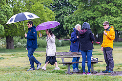 Licensed to London News Pictures. 13/05/2021. London, UK. A family make the most of the bad weather with a breakfast bap and coffee on Wimbledon Common in south west London this morning as miserable May continues with grey skies and rain with temperatures down to 12c today. Weather forecasters predict sunshine and showers for most of the weekend and next week with chilly nights in the South East. Photo credit: Alex Lentati/LNP