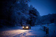 Small car drives slowly on icy road in The Cotswolds, Swinbrook, Oxfordshire, United Kingdom