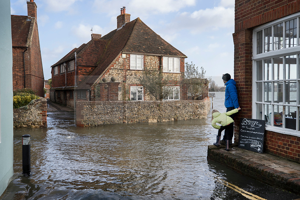 © Licensed to London News Pictures. 03/01/2018. Bosham, UK. Visitors to Bosham look at high tidal flood water in the High Street as storm Eleanor hits the south. Winds of up to 80 mph are being forecast today in parts of the UK. Photo credit: Peter Macdiarmid/LNP
