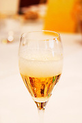 A champagne glass flute filled with Gosset Grand Reserve champagne against a backdrop of a white table cloth with the mousse foam frothing, Restaurant Les Berceaux, Patrick Michelon, Epernay, Champagne, Marne, Ardennes, France