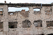 Building in Mostar damaged by the war and still not renovated. Ruined by bullet holes, mortar bomb shell grenade damage, very close to the beautifully renovated old town city centre. Town of Mostar. Federation Bosne i Hercegovine. Bosnia Herzegovina, Europe.