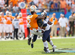 Sep 1, 2018; Charlotte, NC, USA; West Virginia Mountaineers safety Toyous Avery (3) hits Tennessee Volunteers quarterback Jarrett Guarantano (2) after a throw during the first quarter at Bank of America Stadium. Mandatory Credit: Ben Queen-USA TODAY Sports