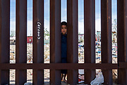 A young Mexican boy is pictured peering from the Mexican side of the Border Fence in Anapra, near El Paso, Texas on Saturday April 7th. Days after Trump has ordered National Guard Troops to be deployed along the US-Mexico Border, many people in El Paso do not see a need for the added security.