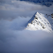 A view on a cross of a summit of a Goldberg group mountain as fog rises, seen from Sonnblick summit at 3,106 meters above sea level, in the Hohe Tauern mountain range near Rauris, Austria, November 23, 2018. REUTERS/Lisi Niesner