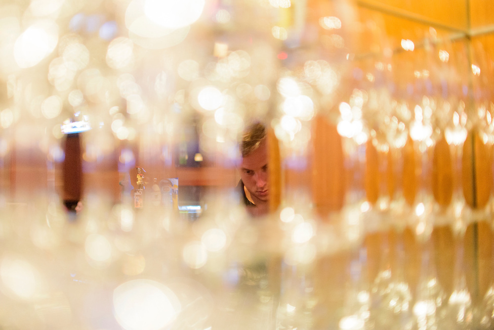 Photo by Matt Roth<br /> Assignment ID: 30144892A<br /> <br /> Vince Ritter, 25, reflected in a mirror behind wine glasses, bar-tends at the Shanty Grille in Ellicott City, Maryland Saturday, July 06, 2013. He turns 26 the following Monday and will be kicked off his parents health insurance plan. He will start a new full-time job with benefits at First Mariner Bank the week after his birthday. He still plans to work at Shanty Grille, but only on the weekends.