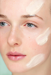 Young Woman with Moisturizing Cream on Face
