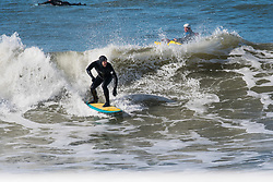 © Licensed to London News Pictures. 15/03/2017. Aberystwyth, Wales, UK. A man enjoying surfing the waves on a  day of clear blue skies and brilliant unbroken warm springtime sunshine in Aberystwyth Wales. Photo credit: Keith Morris/LNP