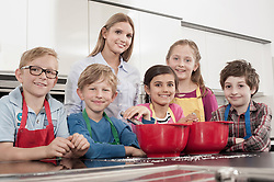 Teacher with student baking in home economics class, Bavaria, Germany