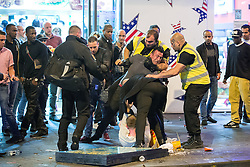 © Licensed to London News Pictures . 15/06/2014 . Manchester , UK . Two men fight and have to be pulled apart by security , outside a takeaway . People on a night out in Manchester City Centre overnight , following England's defeat to Italy in the World Cup . Photo credit : Joel Goodman/LNP